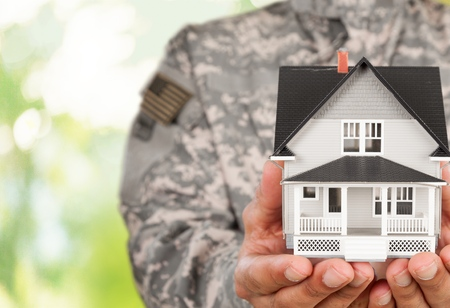 Soldier Holding a Model of House Stock Photo