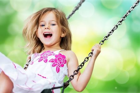 Blondes Mädchen des kleinen Kindes, das Spaß auf einer Schaukel hat