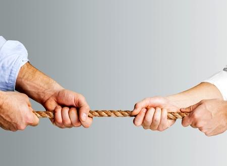 Tug war, two businessman pulling a rope Фото со стока