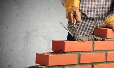 Bricklayer worker installing brick masonry on exterior Stock Photo