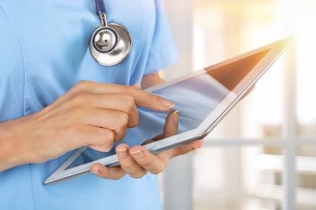 Ärztin, die auf digitalem Tablet arbeitet