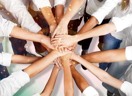 Grupa ludzi układających ręce razem