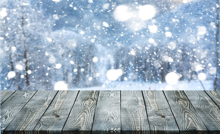 Empty wooden surface for product montage with falling snow and nice view of Christmas trees in winter time.           - Image