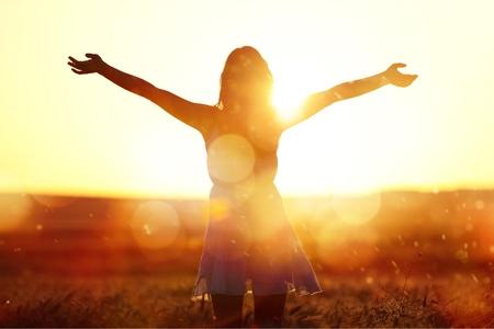 Junge Frau auf Feld unter Sonnenuntergangslicht