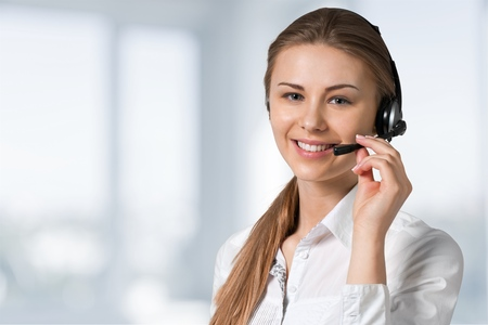 Young female call center employee on light background
