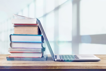 Stack of books with laptop on wooden table Standard-Bild