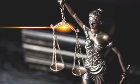Primer plano de una escultura de Themis, diosa mitológica griega, símbolo de la justicia, ciega y con el equilibrio vacío en la mano. Foto de archivo