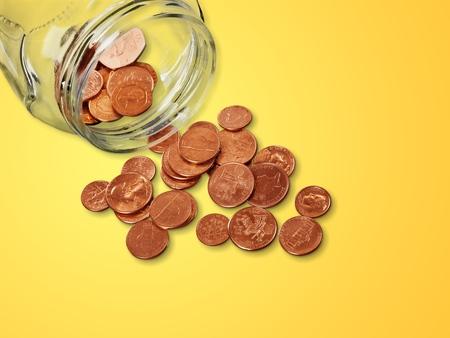 Jar of pennies spilling out on refective white Reklamní fotografie