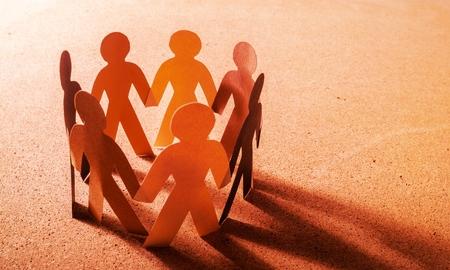 Gente de papel en un círculo cogidos de la mano