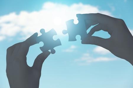 Mani che mettono i pezzi del puzzle