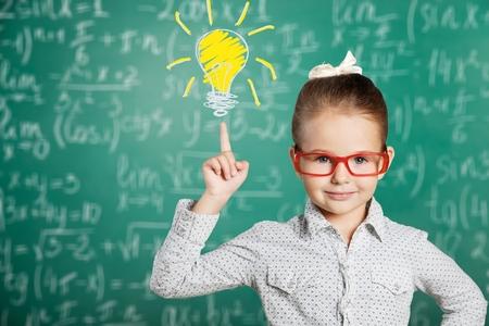 Cute little schoolgirl ineyeglasses pointing with finger