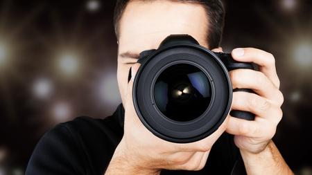 Mężczyzna fotograf z aparatem w tle