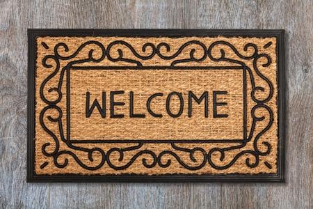 Neue Willkommensfußmatte auf Holzboden Standard-Bild