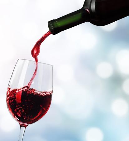 Verter el vino tinto en vaso aislado sobre fondo blanco.