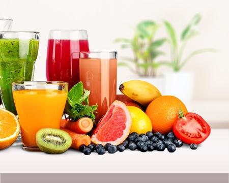 Gustosi frutti e succhi con vitamine sullo sfondo