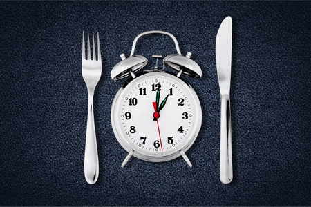Alarm clock with knife and fork  for mealtime or diet concept