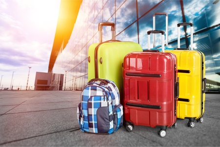 Two suitcases in airport terminal waiting area, business travel or vacation concept, luggage in departure airport hall, flare light, blank space for text message or logo