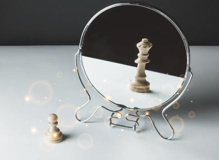 Peón de ajedrez mirando en el espejo y