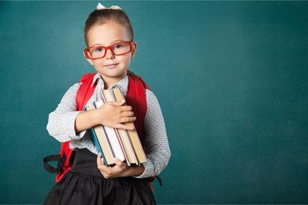Piccola studentessa carina con gli occhiali sulla lavagna