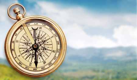 Brass antique compass on background