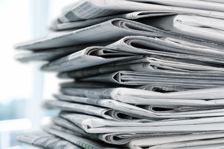 Montón de periódicos impresos sobre fondo blanco.