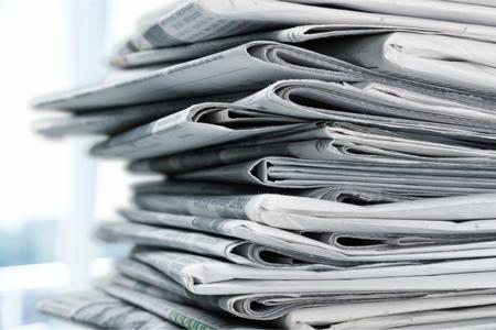 Stos drukowanych gazet na białym tle