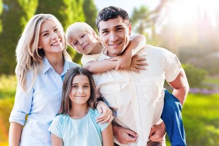 Belle famille charmante souriante sur le parc