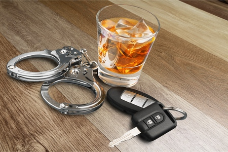 Whiskey with car keys and handcuffs concept for drinking and driving Stock Photo