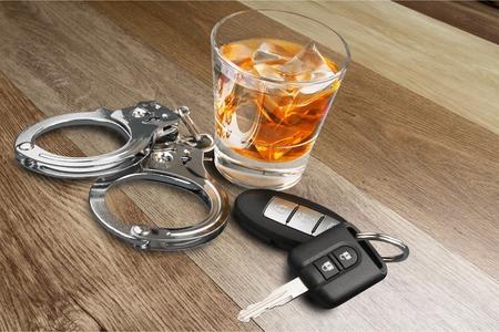 Whisky con llaves del coche y concepto de esposas para beber y conducir Foto de archivo