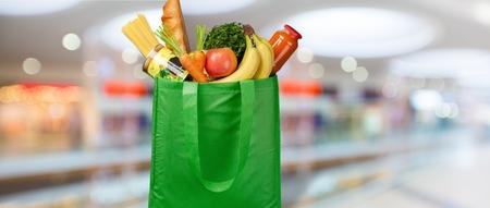 Eco-vriendelijke herbruikbare boodschappentas gevuld met groenten op een wazige achtergrond Stockfoto