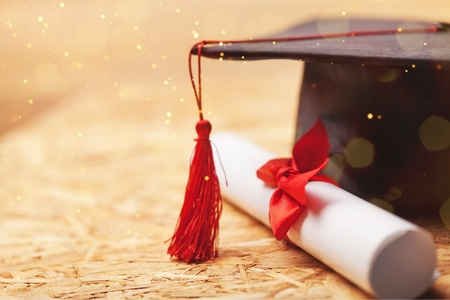 Graduation hat and diploma on wooden background Banque d'images