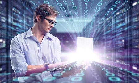 Jeune homme d'affaires avec un ordinateur portable en aluminium moderne et mince dans la salle des serveurs du réseau Banque d'images