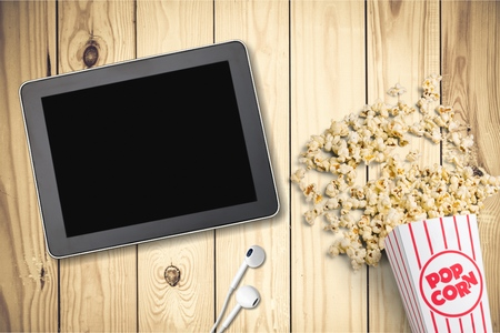 Table with popcorn bottle and logo and earphone. is a global provider of streaming movies and TV series. Stock Photo