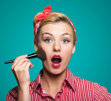 Cute pin up girl applying blusher Imagens
