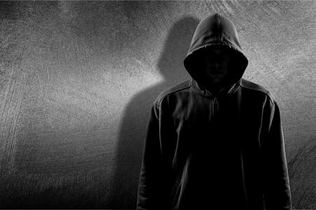 Hombre oscuro irreconocible con capucha en el fondo Foto de archivo