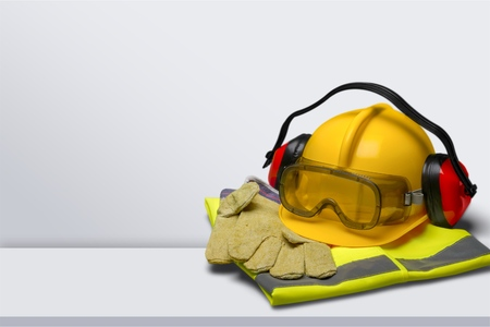 Safety helmet with earphones and goggles on construction background Archivio Fotografico - 124554349