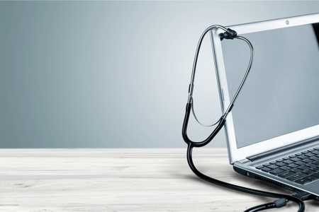 Laptop diagnosis with stethoscope on background Foto de archivo