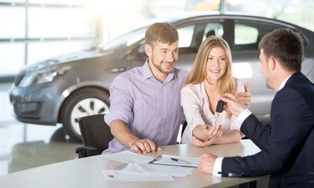 Glückliches Paar mit Autohändler
