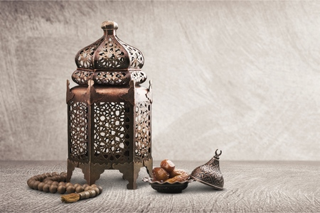 Vintage silver Moroccan, Arabic lantern with glowing candle, green branches, rose flowers and pink petals on white table background. Greeting card for Muslim holiday Ramadan Kareem. Shaby wall.          - Image Stockfoto