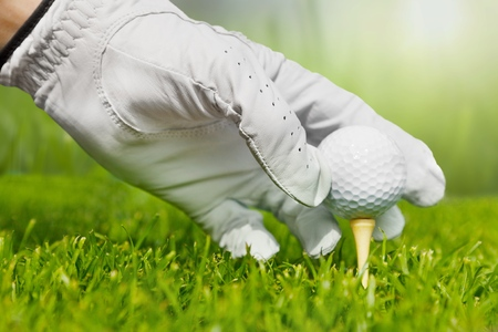 Golfer is putting golf ball on green grass at golf course for training to hole  with blur background and sunlight ray          - Image Stock Photo