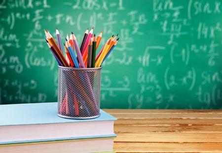 Formules mathématiques écrites à la craie sur le fond du tableau noir.