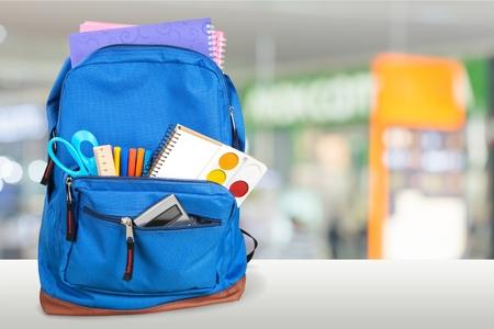 Schulrucksack mit Briefpapier auf Holztisch