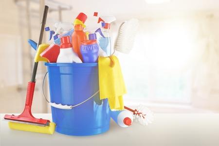 Plastic flessen, schoonmaakhandschoenen en emmer op witte achtergrond