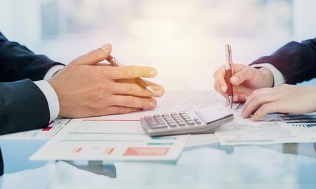 Gráfico de informe de resumen de análisis de inicio de negocios y uso de una calculadora para calcular los números.