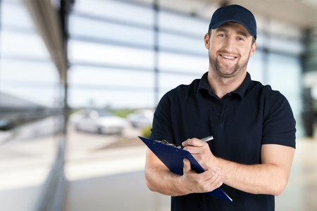 Delivery man with clipboard on light background