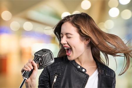 Jonge vrouw met hoed die in de microfoon zingt Stockfoto