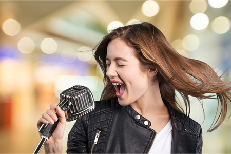 Young woman wearing hat singing into microphone Stock fotó