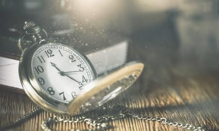 Montre de poche vintage sur une surface en bois contre un vieux livre