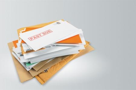 Pila de sobres con facturas de servicios atrasados aislado en blanco Foto de archivo