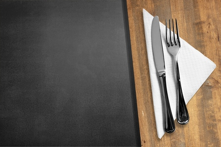 Knife and Fork on Slate and wood background